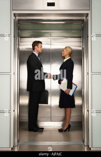Businesspeople shaking hands in Elevator, side view - Stock Image