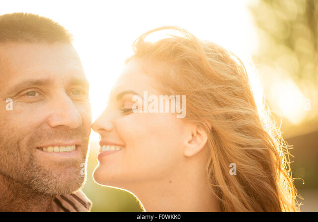Happy couple having great time together - photographed at sunset against sun - Stock Image