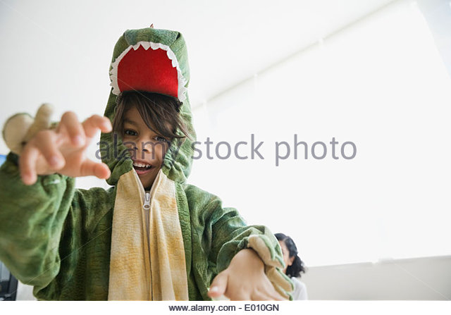 Playful boy in dragon costume - Stock Image