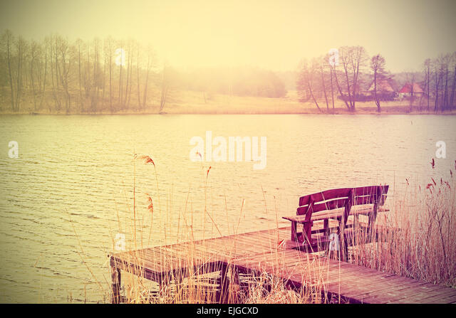 Vintage stylized photo of a wooden bench at the lake. - Stock-Bilder