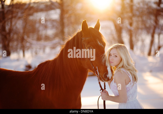 Young woman in white dress with horse in winter - Stock Image