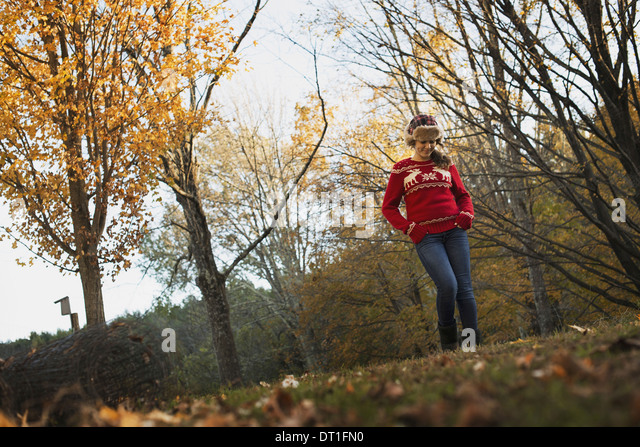 Autumn foliage on the trees on a farm A young girl in a red knitted jumper with a warm tartan woolly hat - Stock Image