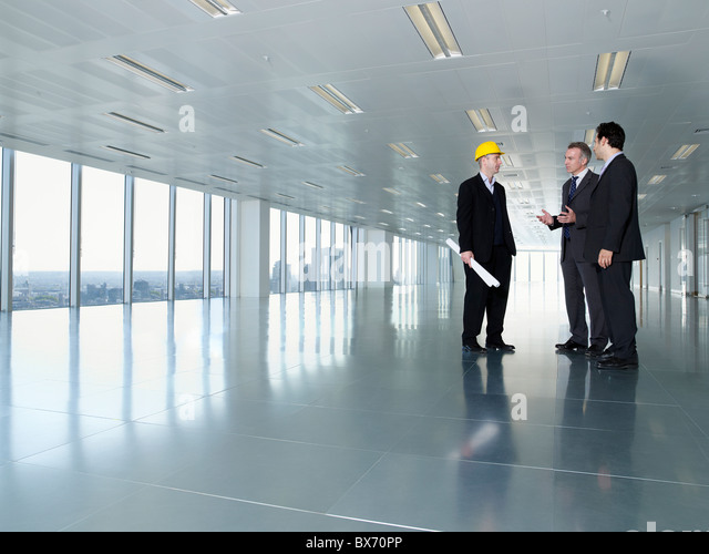 Three executives, one in hardhat, in empty office space - Stock Image