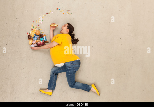 Woman eating food against beige background - Stock Image