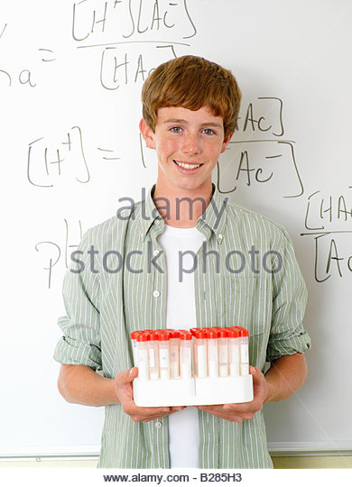 Boy (10-12) with chemistry samples by whiteboard, portrait - Stock Image