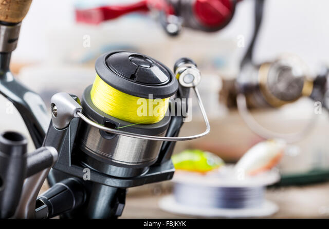 closeup fishing rod with reel on background of tackles in boxes with baits, lure, wobblers - Stock-Bilder