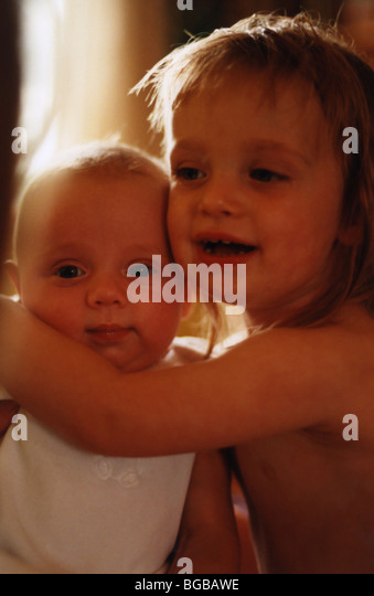 Photograph of young sisters cuddle baby toddlers children family - Stock-Bilder