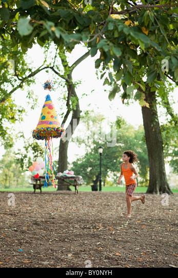 Girl at birthday party running past pinata - Stock-Bilder