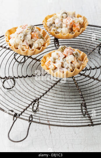 Russian traditional salad olivier in portioned baskets tapas buffet on blue background - Stock Image