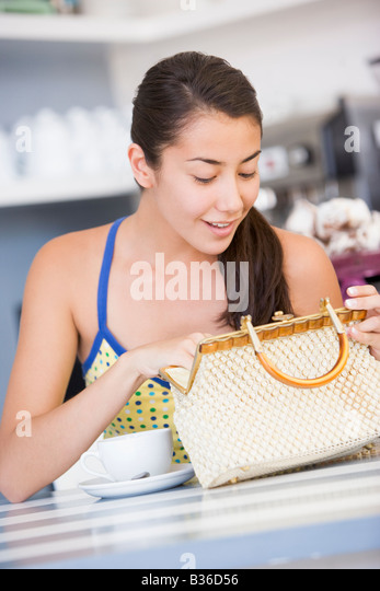 Young woman sitting at a table checking her handbag - Stock Image