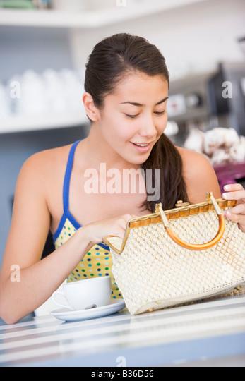 Young woman sitting at a table checking her handbag - Stock Image