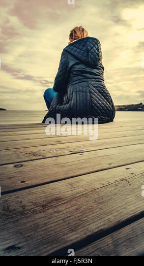 young blond woman siting on wooden floor on the beach - Stock-Bilder