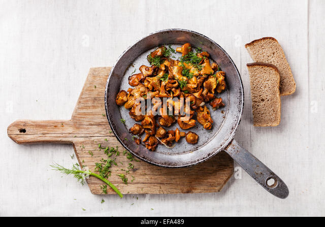 Roasted wild forest  mushrooms in pan on white textured background - Stock Image