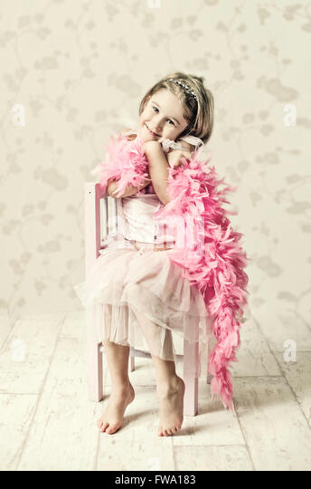 young girl in fancy dress sitting on wooden chair holding feather scarf and posing - Stock Image