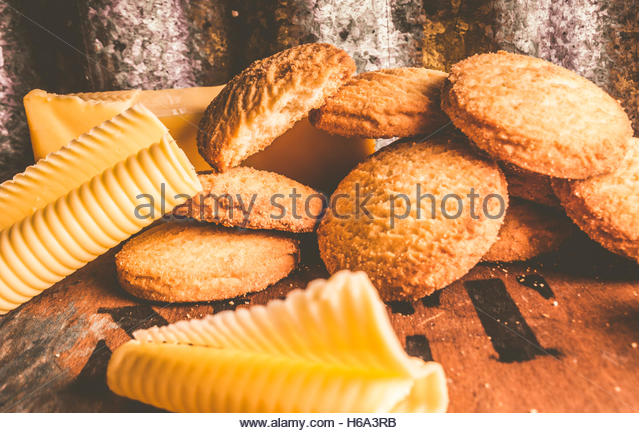 Low view on round vintage cookie food artwork with a batch of old creamy butter shortbread biscuits on retro wooden - Stock Image