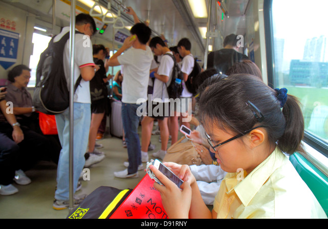 Singapore Kallang MRT Station East West Line subway train public transportation riders commuters Asian teen girl - Stock Image