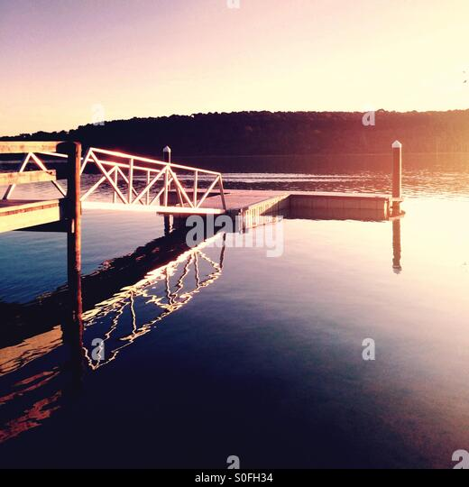 Peaceful lake with jetty and late afternoon sun - Stock Image