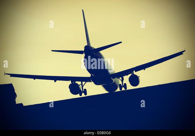 Airplane over roof approaching airport Berlin Tegel, Germany - Stock Image