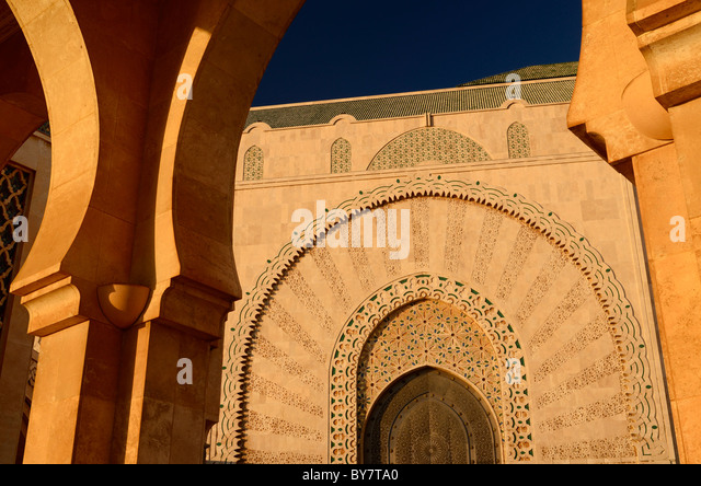 Doorway to the Hassan II Mosque Casablanca at sunset seen through stone archway Morocco - Stock Image