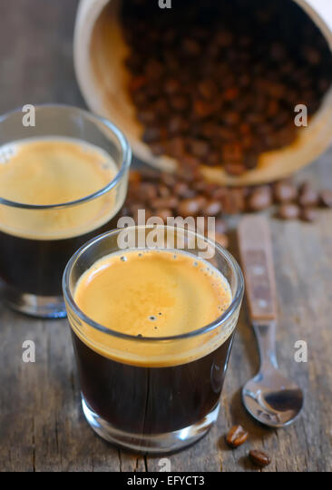 Espresso and Roasted steaming coffee beans - Stock Image