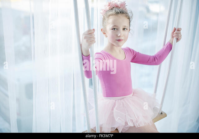 Sad little girl sitting on a swing - Stock Image