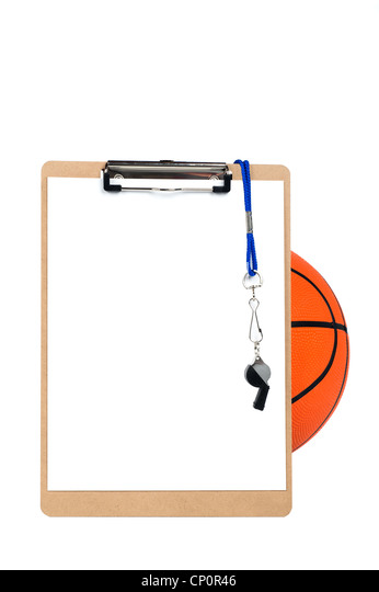 A coach's clipboard with blank sheet of paper, whistle and pencil rests against a basketball and is isolated - Stock Image