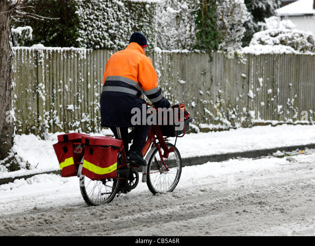 Postman Riding a Bicycle In The Snow Surrey England - Stock Image