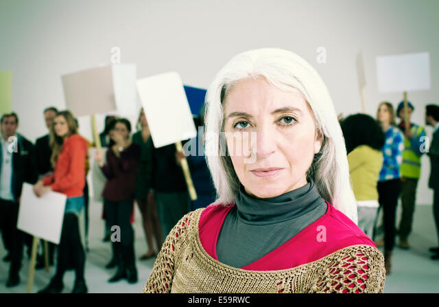 Portrait of serious woman with protesters in background - Stock Image