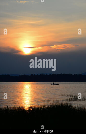 Fisherman in a small boat on lake at sunset on Lake Pleasant in the Adirondack Park, NY. - Stock Image