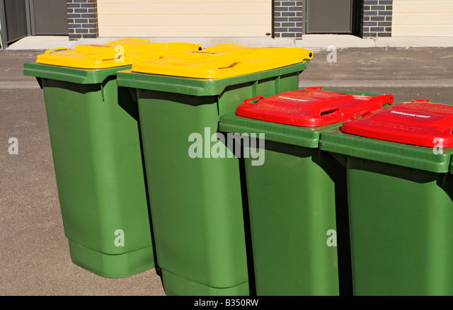 Waste Management / Two Recycle bins and two Garbage bins stand ready for collection. - Stock Image