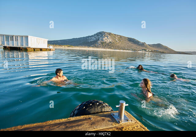 Young adult friends swimming in sunny summer ocean - Stock-Bilder