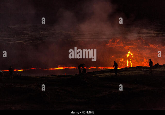 People watch the moving lava lake from the rim - Stock Image