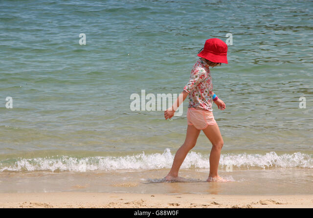 Side view of girl walking on beach - Stock Image