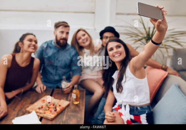 Group of friends having a party on the rooftop making a selfie to remember this perfect moment. Happy and joyful - Stock Image