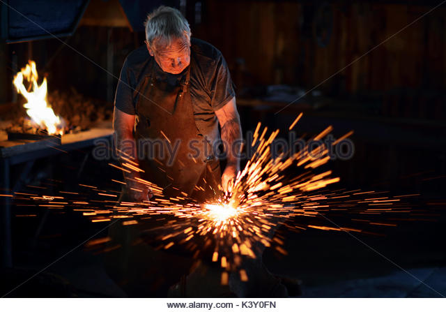 Sparks flying when Authentic Old-Fashioned Blacksmith hit red hot molten iron with hammer on the anvil in his old - Stock Image