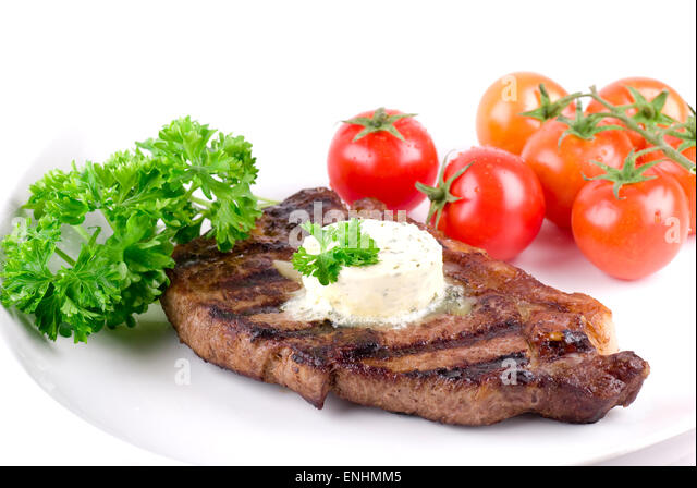 Strip steak with parsley butter on a white plate. Parsley and tomatoes garnish. - Stock Image