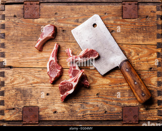 Raw fresh lamb ribs and meat cleaver on wooden background - Stock Image