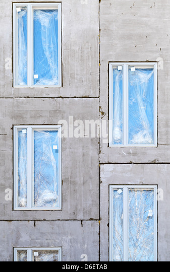 Unfinished building concrete wall with windows. Vertical background - Stock-Bilder