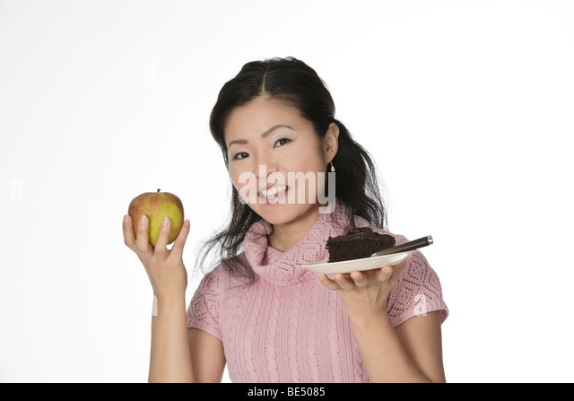 Cute Asian woman trying to make a decision between eating healthy or not - Stock Image
