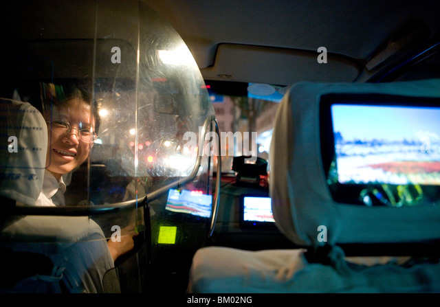 Taxi Shanghai, female taxi driver, protection shield, TV Screen, happy, laughing, happy, happiness - Stock-Bilder