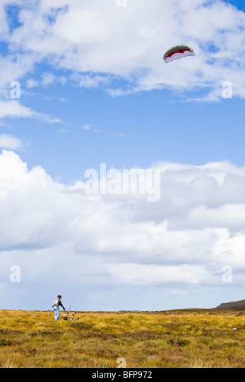 Two brothers struggling to fly a power kite in high winds on moorland east of Syre, Sutherland, Highland, Scotland - Stock Image