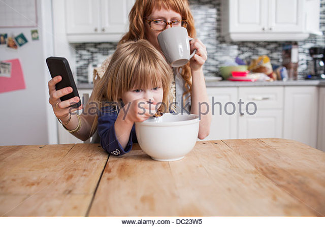 Girl eating breakfast, mother drinking coffee & looking at smartphone - Stock-Bilder