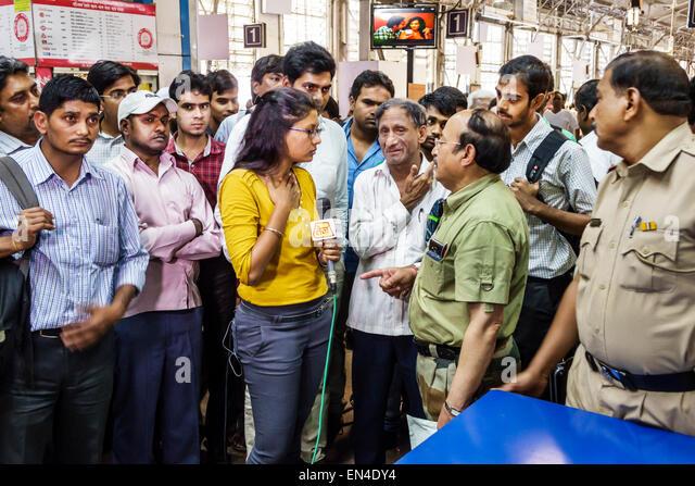 Mumbai India Asian Churchgate Railway Station Western Line train public transportation woman TV reporter media microphone - Stock Image