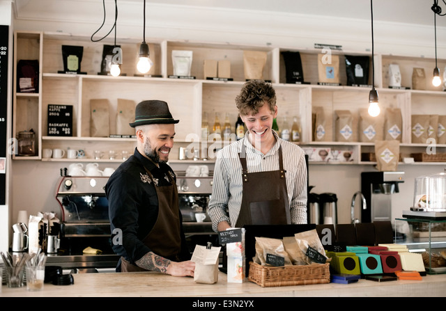 Happy workers working at cafe counter - Stock-Bilder