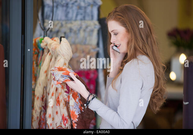 Woman on smartphone shopping for scarf - Stock Image