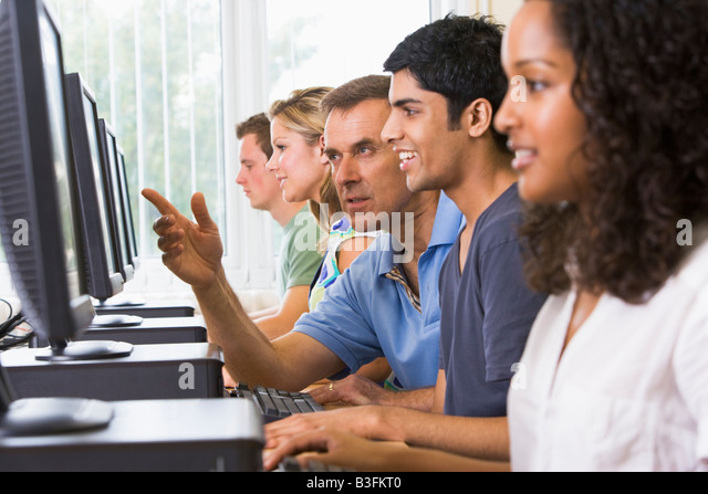 Four students sitting at computer terminals with teacher helping one of them (depth of field/high key) - Stock Image