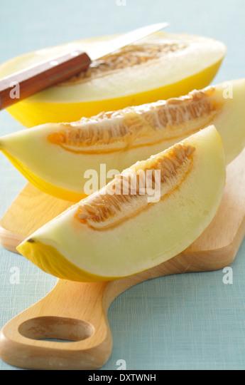 Slicing a yellow melon - Stock Image