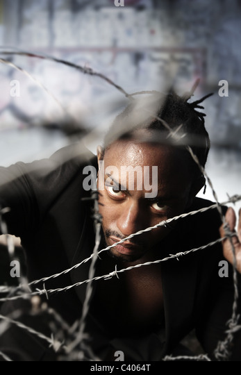 Portrait of a man holding barbed wire and a graffiti wall in background - Stock Image