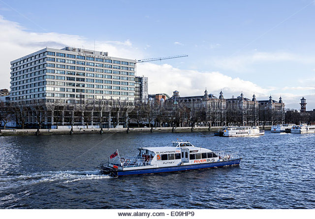 St Thomas' Hospital with Blackfriars to Putney River Bus in foreground, London, England, UK - Stock Image