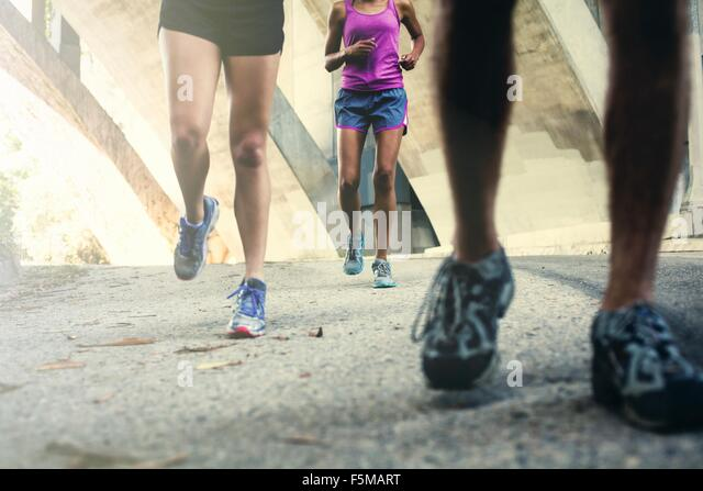 Joggers running on bridge - Stock-Bilder